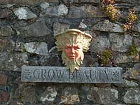 'Grow Beauty' sign on wall at allotment site.