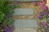 Thyme edged paving and gravel path.  A Gift For Life Saga garden. Hampton Court Flower Show, 2003, London, UK.