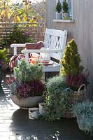 White painted bench on terraced balcony with large autumnal containers planted with evergreen perennials and shrubs.