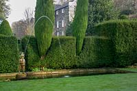 'Fireman' fountain in a pond featuring evegreen shaped Yew hedging in the bakground, 