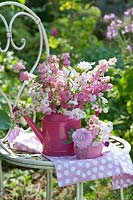 Bouquet of Delphinium - Larkspur and sweet peas in pink watering can.