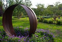 Rusted steel sculpture inspired by a Russian wedding ring designed and made by Dominic Watts. Underplanted with Geranium Rozanne 'Gerwat'.