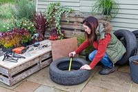 Woman taking measurements for base of tyre planter.