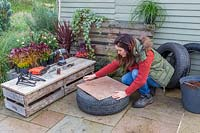 Woman marking out circle on sheet of hardboard, to create base for tyre planter.
