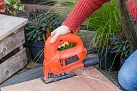 Woman using jigsaw to cut circle of hardboard for base of planter.