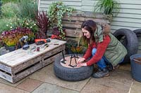 Woman marking out where metal legs for type planter will be attached.