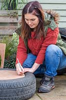 Woman marking where to make holes in base of planter to attach to tyre.