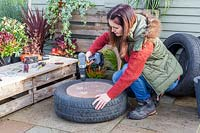 Woman using a drill to create drainage holes in base of tyre planter.