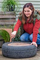 Woman using washers and bolts to secure wooden base onto tyre planter.