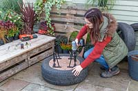 Woman securing metal legs to base of tyre container.