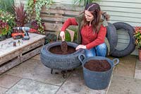 Woman adding compost into tyre container.