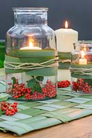 View of woven Phormium table mat and glass candle holders, decorated with Cotoneaster berries.