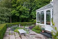 View of terrace patio by conservatory, with outdoor furniture.