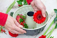 Woman placing red gerbera flowerhead to bundt cake tin.