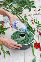 Woman pouring de-ironised water into bundt cake tin full of cut plant material to create frozen floral arrangement.