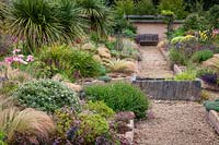 Courtyard garden with raised beds either side of gravel path, beds full of mixed planting