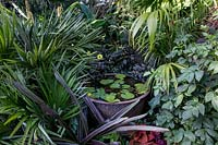 Cauldron water feature surrounded by tropical planting.