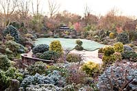 Japanese Tea House-style gazebo in frosted garden, with oriental statuary and shrubs and trees. The Four Seasons Garden, UK.