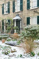 View towards front of house with porch and shutters in a town garden