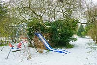 Children's swing and slide set under trees in wild garden with snow.