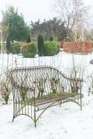 Wire garden seat in country garden in winter.