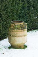 Greek urn beside Taxus baccata - Yew hedge in winter.