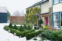 A Buxus parterre beside front door of a victorian house.