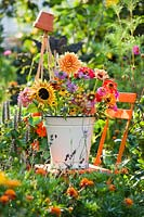 Bucket of summer flowers on chair in colourful cutting garden.