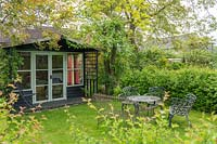 Garden summerhouse with metal table and chairs.