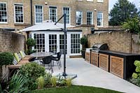 Contemporary back garden with white stone patio, with garden furniture, parasol