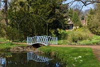 Blue metal arched bridge over pond with, arch supports, lawn, trees