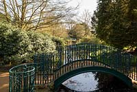 Arched foot-bridge with painted metal railing over water