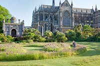 Child running around labyrinth garden planted with alliums, with Cathedral beyond. Arundel Castle, West Sussex, UK.