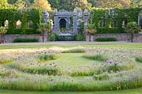 View from labyrinth planted with alliums to domed pergola and Italianate water feature. Arundel Castle, West Sussex, UK.
