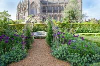 View through rustic arbour to wooden bench and Cathedral beyond. Arundel Castle, Sussex, UK.