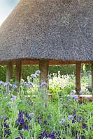Thatched roundhouse with wildflowers