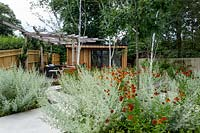 Contemporary white stone paved patio area in London garden with wood garden room and pergola Planting includes: Betula Jackmanii, Artemisia absinthium Lambrook mist. Helenium Moerheim Beauty