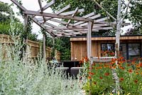 Contemporary patio area in London garden with wood garden room and pergola. Designed by Kate Eyre Garden Design.