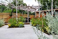 Contemporary white stone paved patio area in London garden with wood garden room and pergola. Designed by Kate Eyre Garden Design.