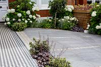 London house and front garden with black and white Victorian style tile path and tiled driveway. Designed by Kate Eyre Garden Design