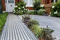 London house with black and white Victorian style tile path with Ilex Crenata Dark Green border and tiled driveway and wood batten bin store in background featuring Hydrangea arborescens Anabelle, 