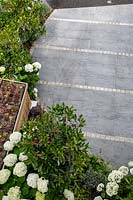 View from above of a front garden with tiled driveway and wood batten bin store with succulent green roof featuring Hydrangea arborescens Anabelle, 