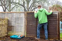 Man repairing wooden fence panels.