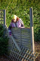 Woman inspecting a storm damaged fence panel.