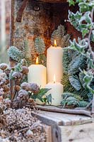 Trio of lit candles in frosted, decorative winter display.