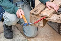 A person using hammer and chisel to loosen the boards from pallet