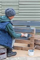 Woman painting the wooden pallet light grey with paint brush