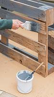 A person painting the wooden pallet light grey with paint brush
