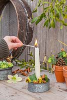 Woman lighting candle in galvanised candle holder decorated with winter flowers, leaves and bark.