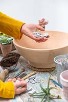 Woman adding stones to the bottom of shallow bowl